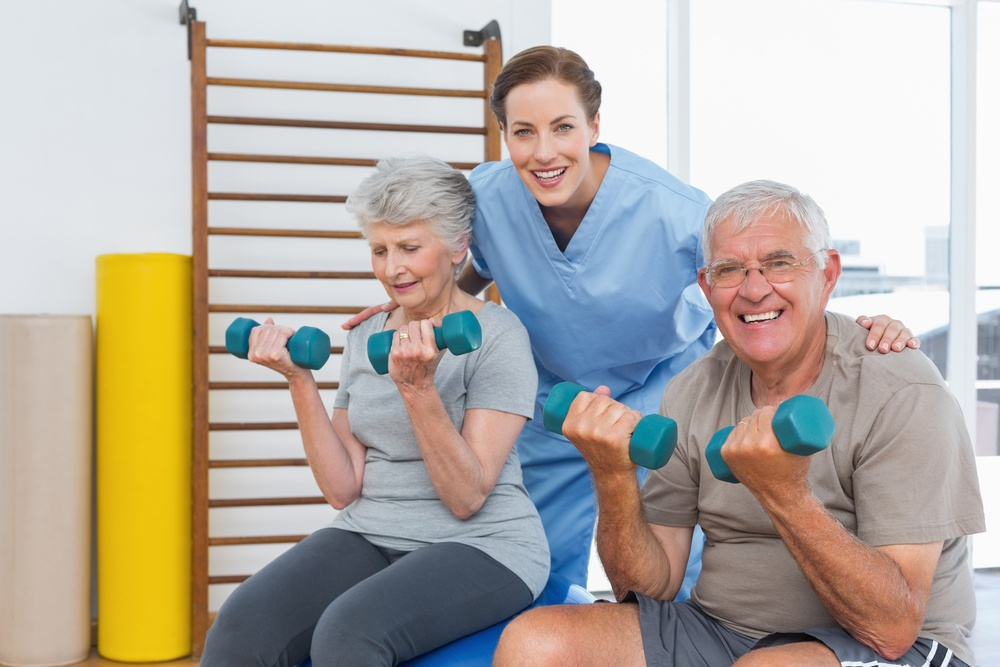 Female therapist assisting senior couple with dumbbells in the medical office.jpeg