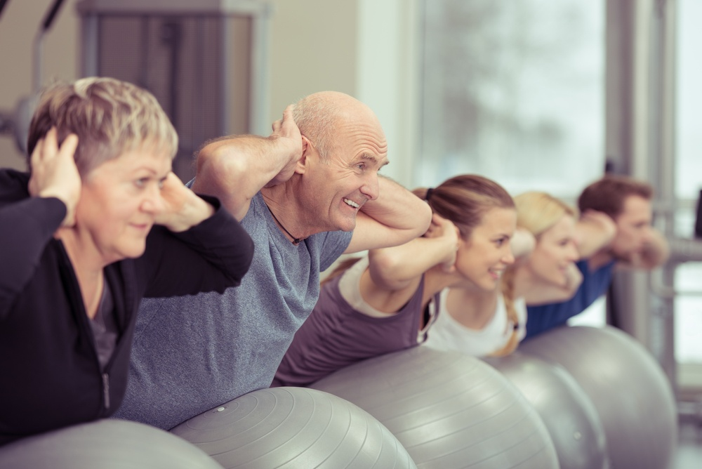 Happy elderly couple exercising in a pilates class at the gym with three other younger people toning and strengthening their muscles using gym balls, focus to the senior man and woman.jpeg